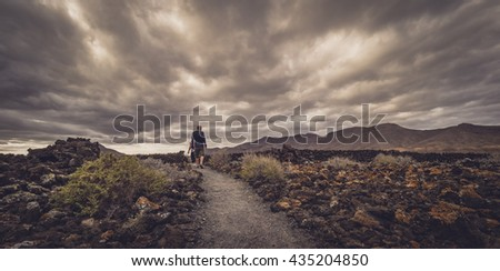 Man walking on a path leading towards the archaeological site of an old aboriginal village in Fuerteventura, Canary Islands, Spain. Picture taken 13 April 2016 - stock photo