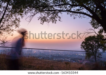 Man walking on a tightrope, jumping into the city night lights slack-line - stock photo