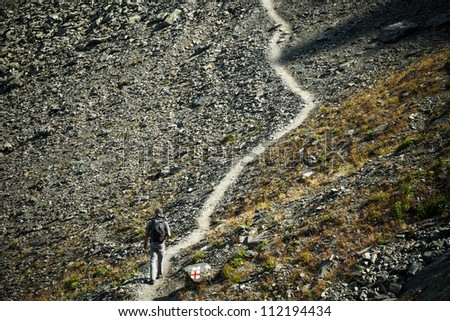 Man walking on mountain trail, hiking to the top - stock photo