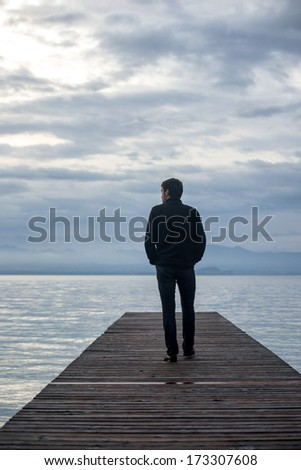 Man walking on pier alone at twilight - stock photo