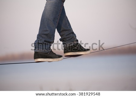 Man walking on slackline - stock photo