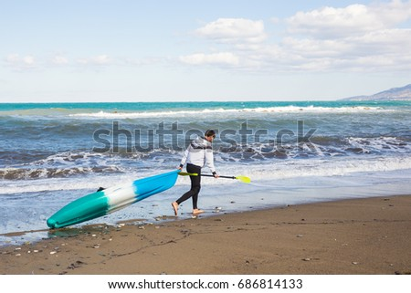 Man walking on the beach with kayak. Traveling by sea. Leisure activities on the water.