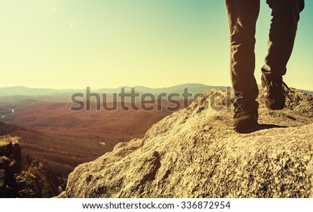 Man walking on the edge of a cliff high above the mountains below - stock photo