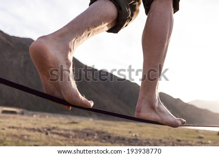 Man walking on the sling at sunset - stock photo