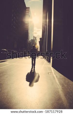 Man walking on the street of New York  at sunrise - stock photo