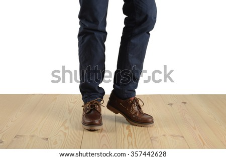 Man walking on wooden floors, detail of the shoes
