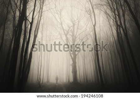 man walking past a huge old tree in a dark spooky forest - stock photo