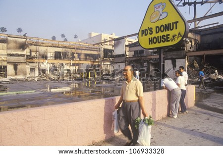 Man walking past donut shop destroyed during 1992 riots, South Central Los Angeles, California - stock photo