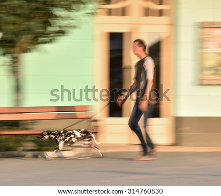Man walking the dog on the street. Intentional motion blur - stock photo