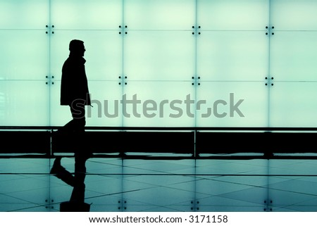 Man walking through an airport terminal - stock photo