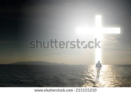 Man walking to a Christian Cross of Light - stock photo