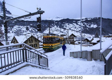 Man walking to fetch a train through a snow covered platform