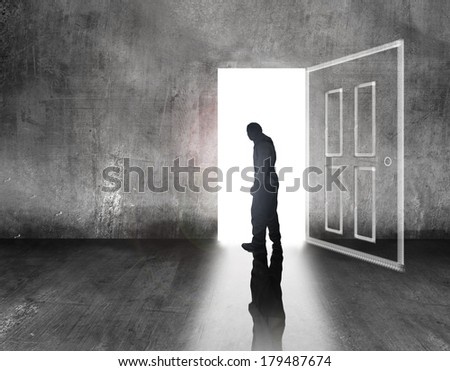 man walking to light door - stock photo