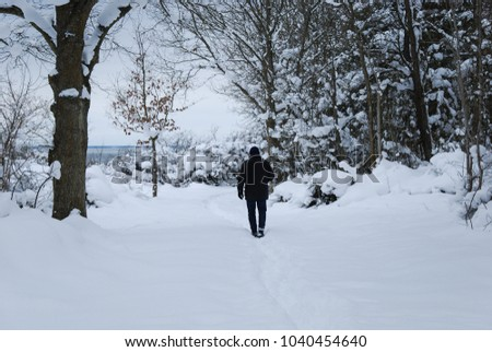 Man walking to the coast on a footpath in a snowy forest