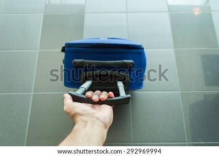 man walking travel bag by an international airport - stock photo
