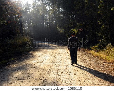 Man walking up dirt road in late afternoon with rays of sun and long shadows - stock photo