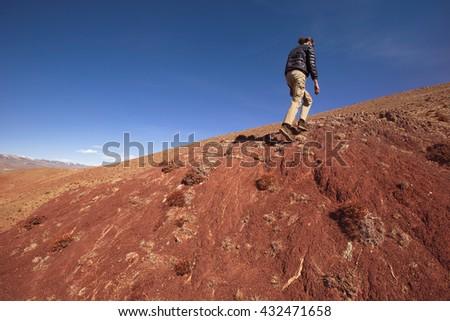 Man walking up on red mountain. hiking summer adventure - stock photo
