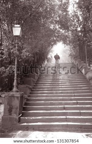 Man Walking up steps to Michelangelo Square, Florence, Italy in Black and White Sepia Tone - stock photo