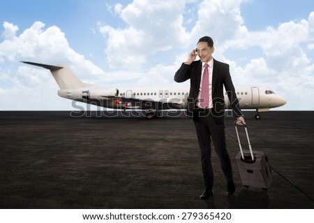 Man walking while calling on the cellphone after arriving with plane. Business travel concept - stock photo