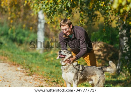 Man walking with a hunting dog - the West Siberian husky. Close-up. Those men are not seen. Autumn. Copy space.