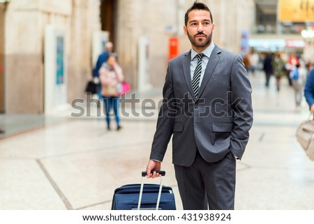 Man walking with a trolley at the station - stock photo