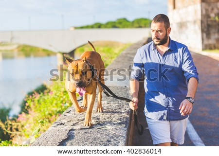 Man walking with his dog. A man  is walking next to the river with his dog on a leash. He is looking at the dog and is wearing summer clothes. On the background there is a bridge and some plants. - stock photo