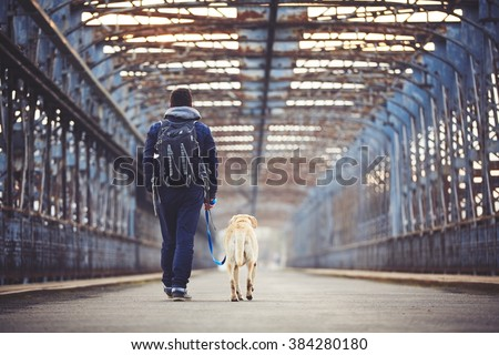 Man walking with his yellow labrador retriever on the old bridge - stock photo