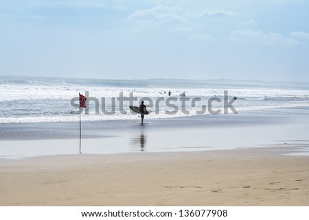 man walking with surfboard under arm along kuta beach in bali indonesia - stock photo