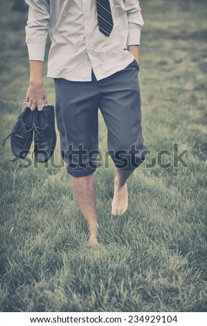Man walks on grass - stock photo