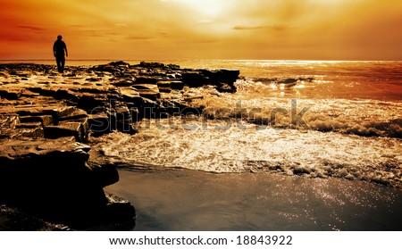 Man walks on rocks at Sea Lion Island at sunset - stock photo