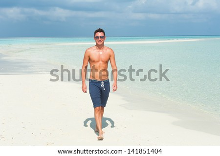 man walks on the beach with the blue sea and the beautiful sky with white clouds