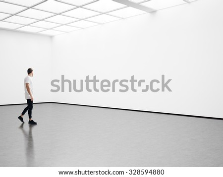 Man walks on the exhibition hall and examines a gallery  - stock photo