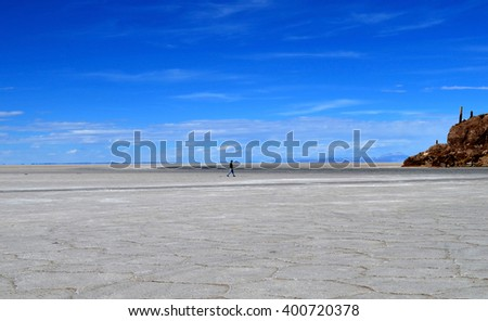 Man walks to Isla Incahuasi (Pescadores), Salar de Uyuni, Bolivia - stock photo