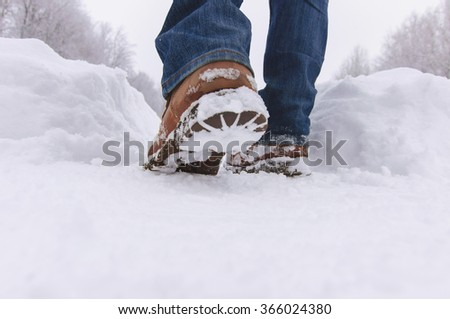 Man walks with boots through deep snow in  winter day. - stock photo