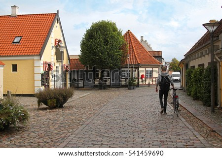 Man walks with his bicycle down a famous cobblestone street in Odense, Denmark, Scandinavia