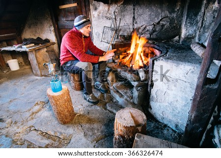 man warm up by the fire in the mountain cabin
