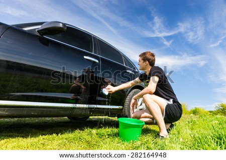 Man Washing Car with Soapy Sponge, Crouching Next to Green Bucket in Green Grassy Field on Bright Sunny Day with Blue Sky - stock photo