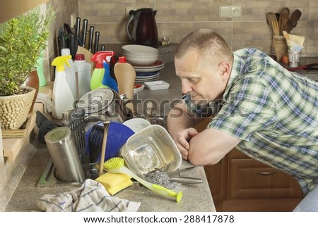 Man washing dirty dishes in the kitchen sink. Domestic cleaning up after the party. - stock photo