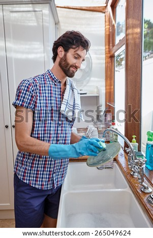 man washing dishes cleaning kitchen at home - stock photo