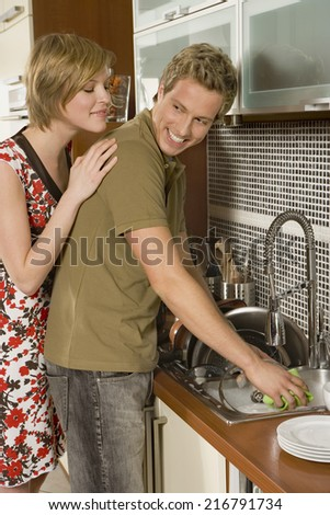 Man washing dishes, woman looks on. - stock photo