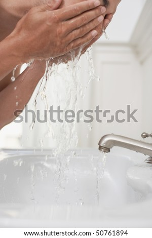 Man washing face in bathroom sink - stock photo