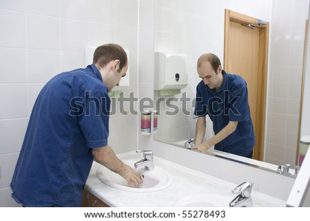 Man washing hands. Public toilet
