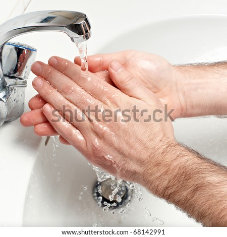 man washing hands under running water