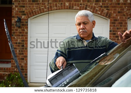 Man washing his car in the driveway