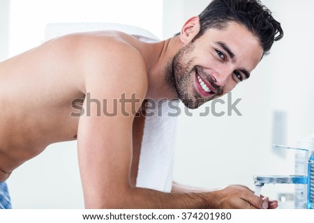 Man washing his face in sink in bathroom - stock photo