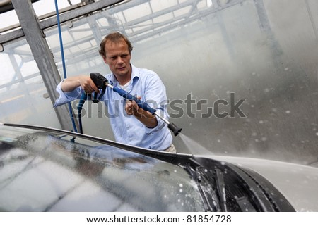 Man washing the windscreen of his car in a cubicle with a high pressure water jet