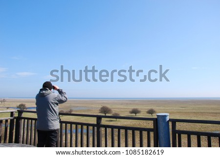 Man watching birds with  binoculars from a tower by the great grassland at Ottenby on the swedish island Oland - a famous birding site