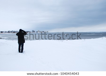 Man watching by an ice covered bay at the swedish island Oland