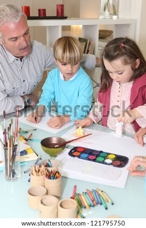 Man watching grandchildren paint - stock photo