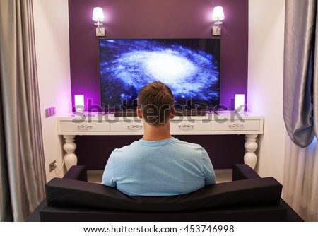 Man watching 4K TV in the living room, view from the back - stock photo